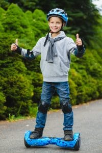 Boy on hoverboard with safety equipment on