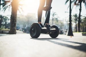 Young hipster girl driving on hoverboard at sunny park